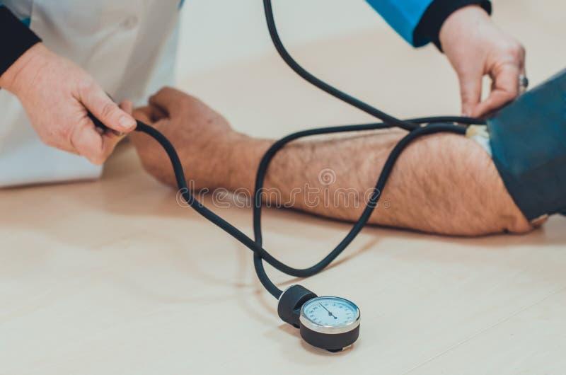 Una presi?n arterial de medici?n del doctor de un paciente masculino con el sphygmomanometer y el estetoscopio fotografía de archivo libre de regalías