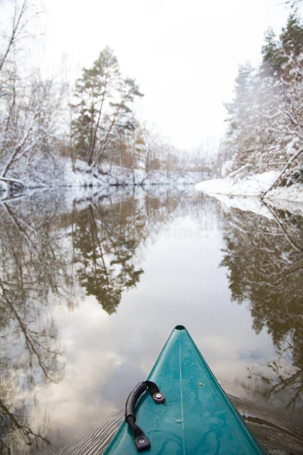 Una primera opinión de la persona de una canoa que se bate a lo largo del río en invierno fotografía de archivo libre de regalías