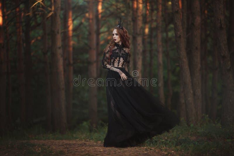 Una princesa gótica hermosa con la piel pálida y el pelo rojo muy largo en una corona negra y un vestido largo negro en un bosque imagen de archivo libre de regalías
