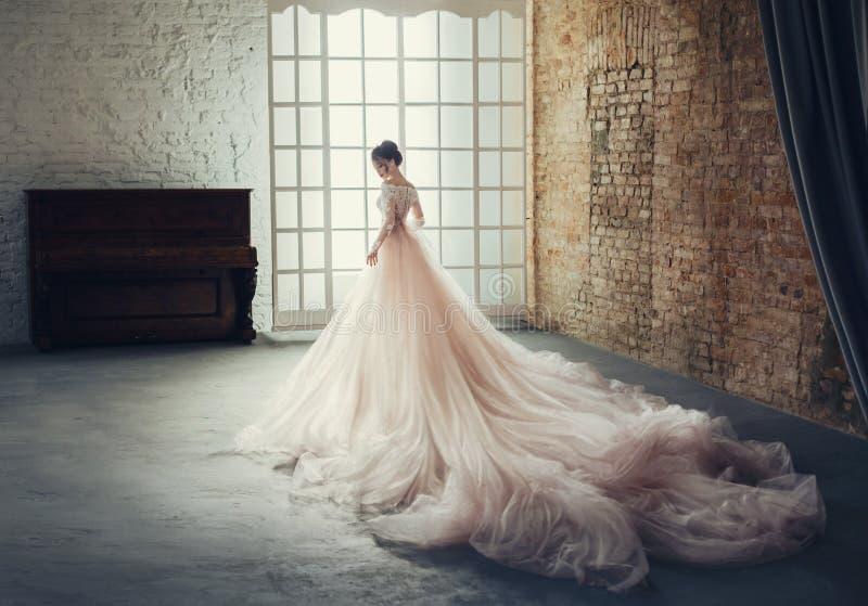 Una princesa joven en un vestido costoso, lujoso con un tren largo se opone con ella de nuevo a la cámara, a imagenes de archivo