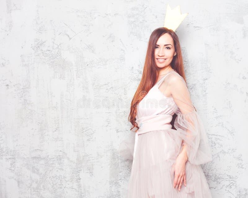 Una princesa La muchacha del pelirrojo en un vestido elegante del aire y el oro coronan en un fondo de una pared de piedra gris fotos de archivo libres de regalías