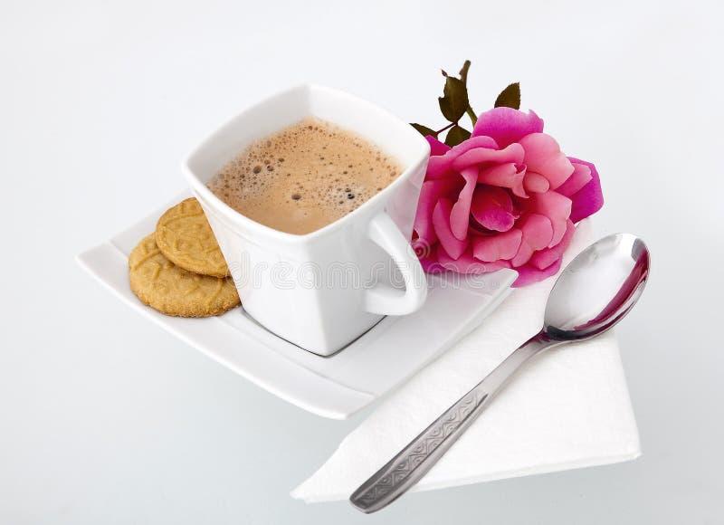 Una protezione di caffè con i biscotti e una rosa fotografia stock libera da diritti