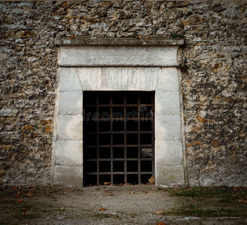 Una puerta con las barras de hierro oxidadas - como una entrada a una mazmorra, a una tumba o a una prisión antigua fotografía de archivo libre de regalías