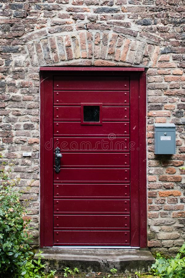 Una puerta de Borgoña en un edificio de ladrillo fotos de archivo