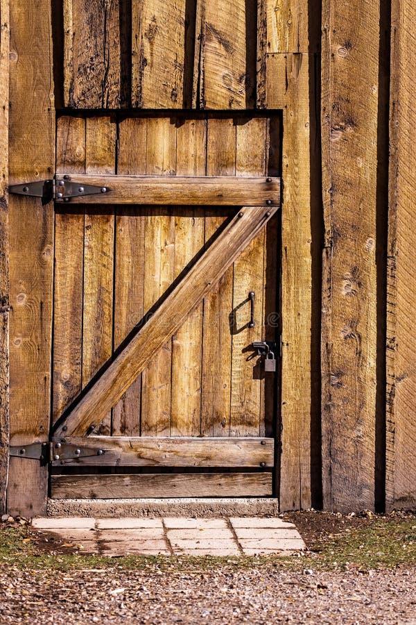 Una puerta de madera pesada, cerrada del exterior, a madera-SID viejo foto de archivo