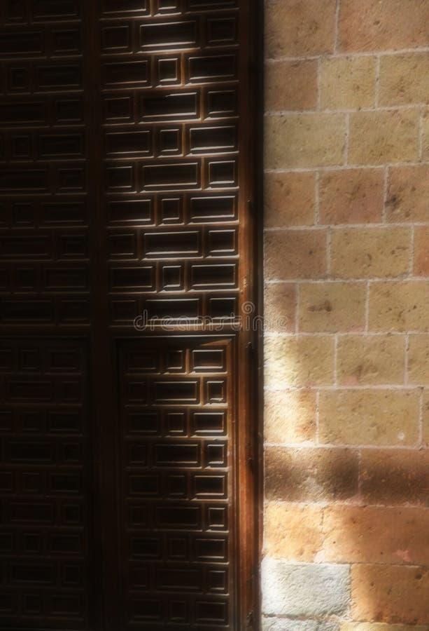 Una puerta de madera y una pared de piedra, con una cuchilla de la luz fotos de archivo libres de regalías