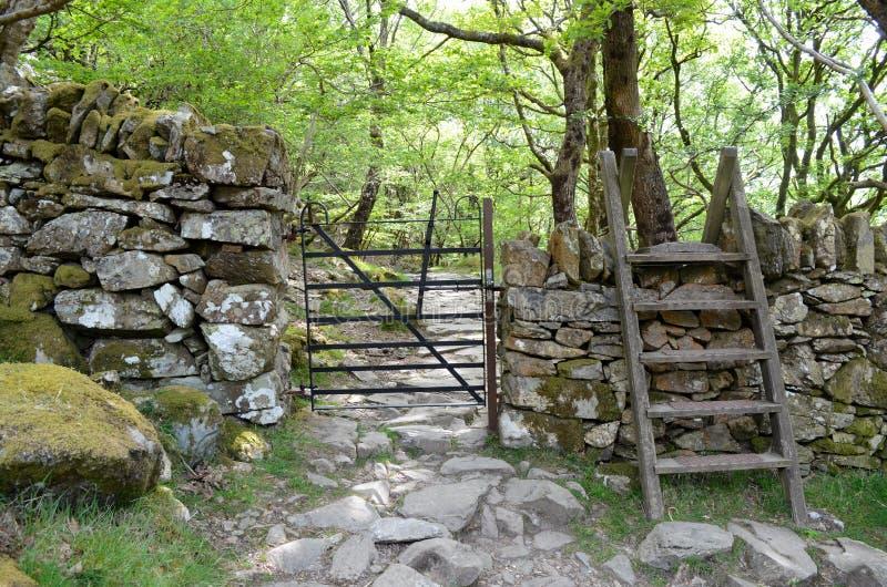 Una puerta del metal a través de una pared y de un montante sobre ella, lleva en una trayectoria rocosa a través de arbolado fotos de archivo