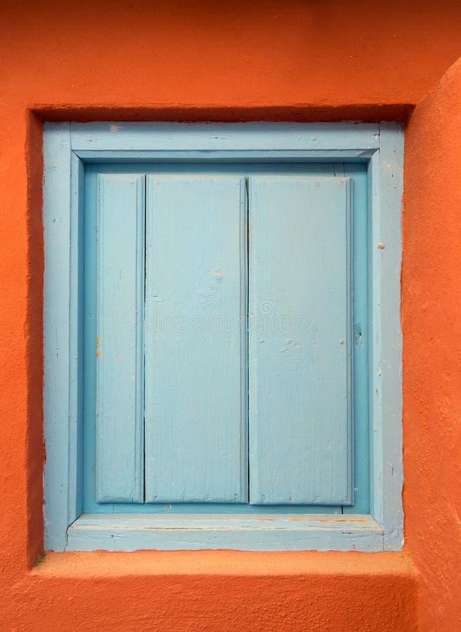 Una puerta o un obturador de madera azul vieja en una pared anaranjada imagenes de archivo