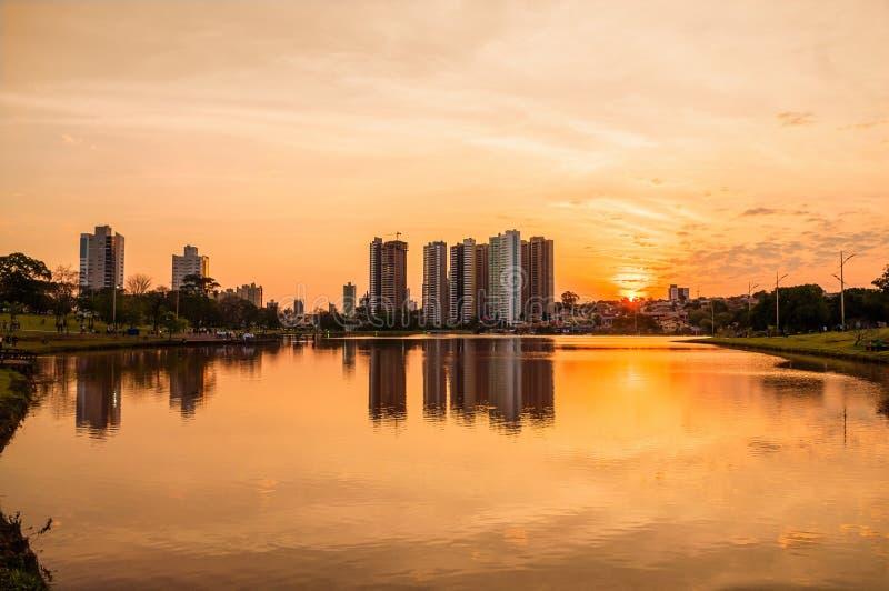 Una puesta del sol caliente hermosa en el lago con los edificios y el fondo de la ciudad Escena reflejada en el agua fotos de archivo