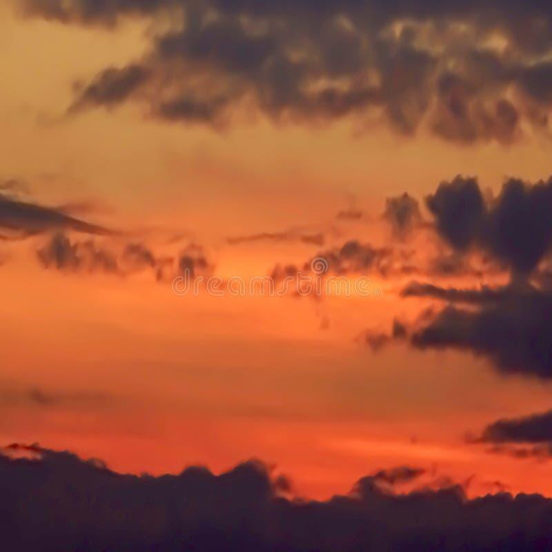Una puesta del sol con las siluetas de nubes y de montañas imagenes de archivo