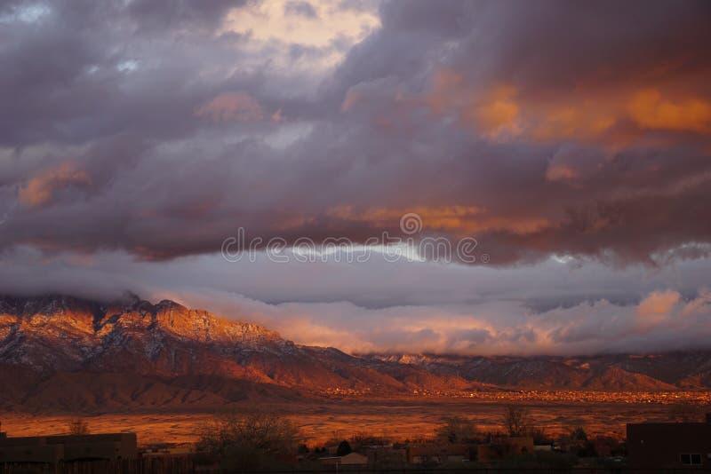 Una puesta del sol de New México con las montañas y las nubes foto de archivo libre de regalías