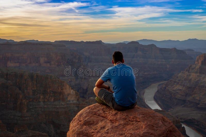 Una puesta del sol de observación del hombre en Grand Canyon imagenes de archivo