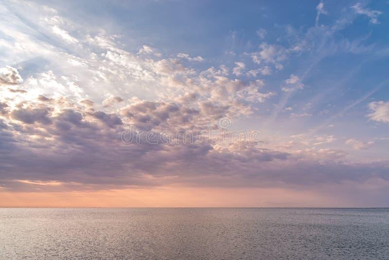 Una puesta del sol hermosa con las nubes magentas y colores hermosos en el mar Nubes hermosas de la salida del sol en el mar foto de archivo