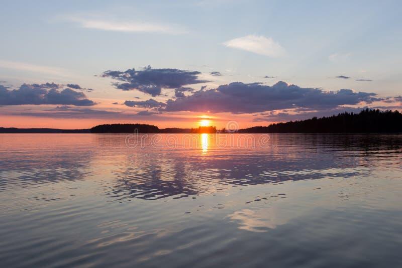 Una puesta del sol hermosa en el lago tranquilo finlandia foto de archivo