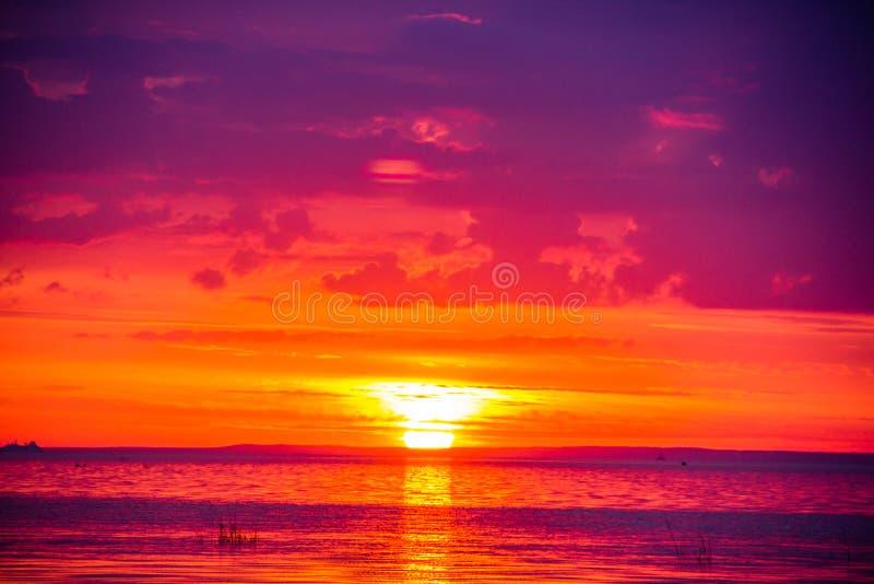 Una puesta del sol inusualmente hermosa del fuego por el mar Puesta del sol en el golfo Puesta del sol en el mar imagen de archivo