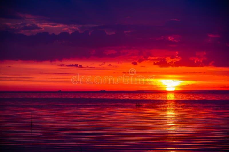 Una puesta del sol inusualmente hermosa del fuego por el mar Puesta del sol en el golfo Puesta del sol en el mar fotos de archivo