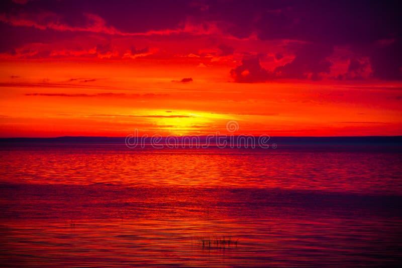 Una puesta del sol inusualmente hermosa del fuego por el mar Puesta del sol en el golfo Puesta del sol en el mar imagenes de archivo