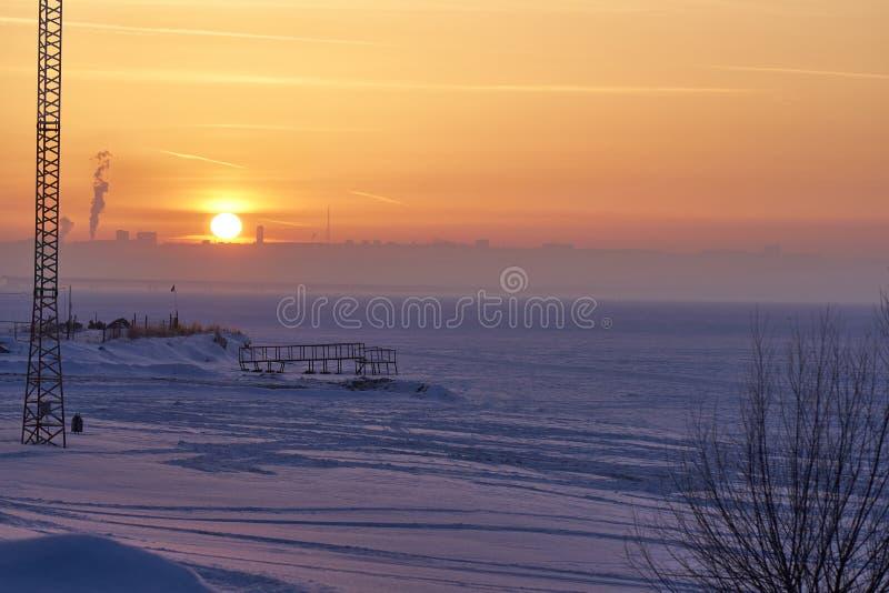 Una puesta del sol del invierno sobre un lago congelado grande En el banco lejano en la neblina son las siluetas visibles de edif imagen de archivo libre de regalías