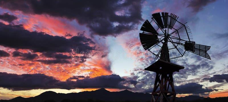Una puesta del sol magnífica, un molino de viento y un horizonte de la montaña imagen de archivo