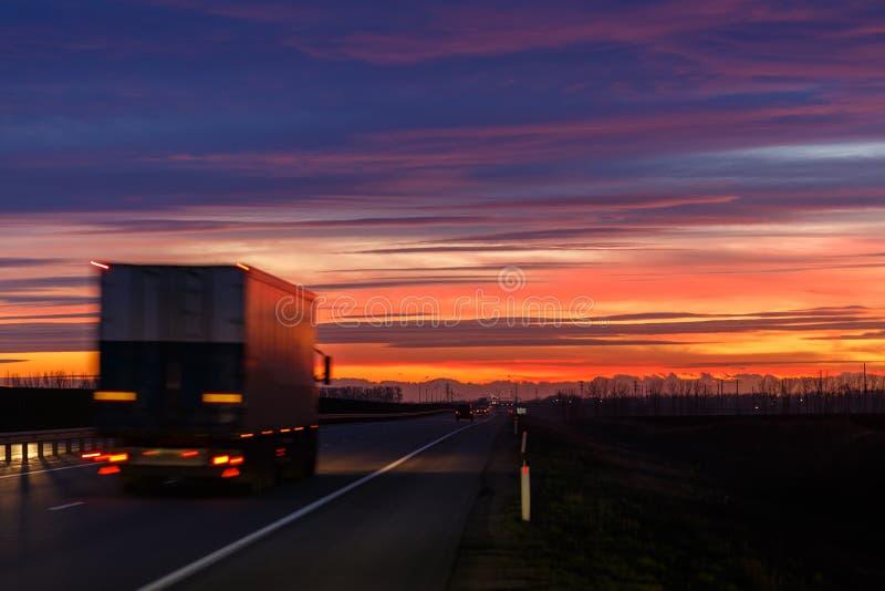 Una puesta del sol muy colorida y una mudanza empañaron el camión en una carretera de asfalto fotos de archivo