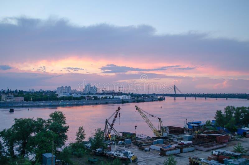 Una puesta del sol rosada hermosa sobre el río de la ciudad Paisaje industrial imagenes de archivo