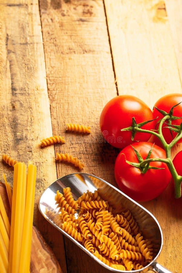 Una puntilla de tomates, del spaggeti italiano y de las pastas En un fondo de madera Fondo culinario Dieta comida sabrosa y sana, fotografía de archivo libre de regalías