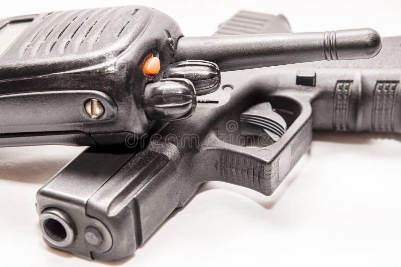 Una radio della polizia che pone sopra una pistola nera di 9mm immagine stock