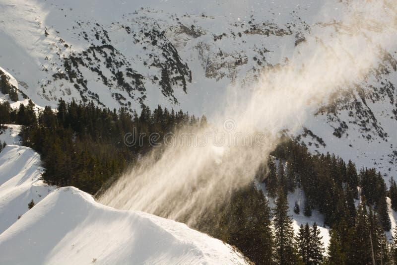 Una raffica di vento soffia la neve nel cielo fotografie stock