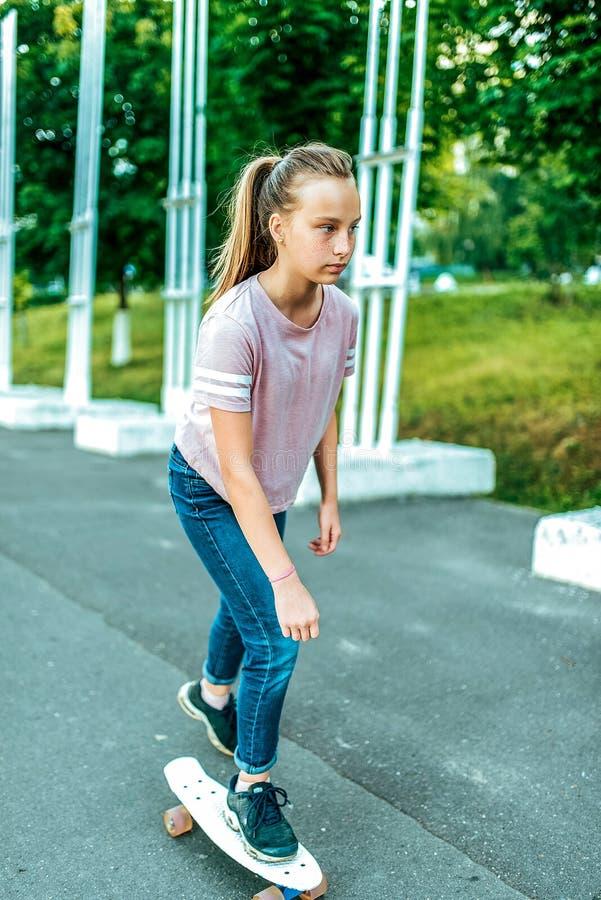 Una ragazza è una scolara di 12-15 anni, guidante un pattino di estate nella città, una strada asfaltata casuale immagini stock libere da diritti