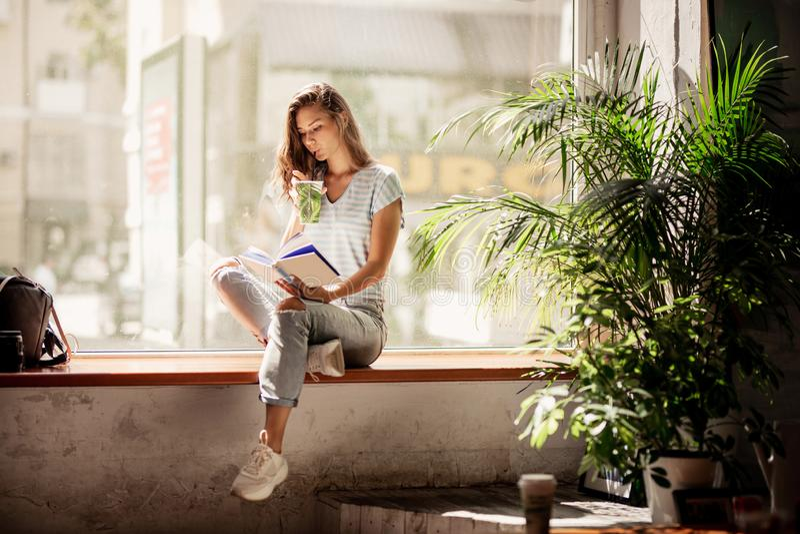 Una ragazza abbastanza esile con capelli lunghi, attrezzatura casuale d'uso, si siede sul davanzale e beve il caffè e legge un li immagine stock libera da diritti