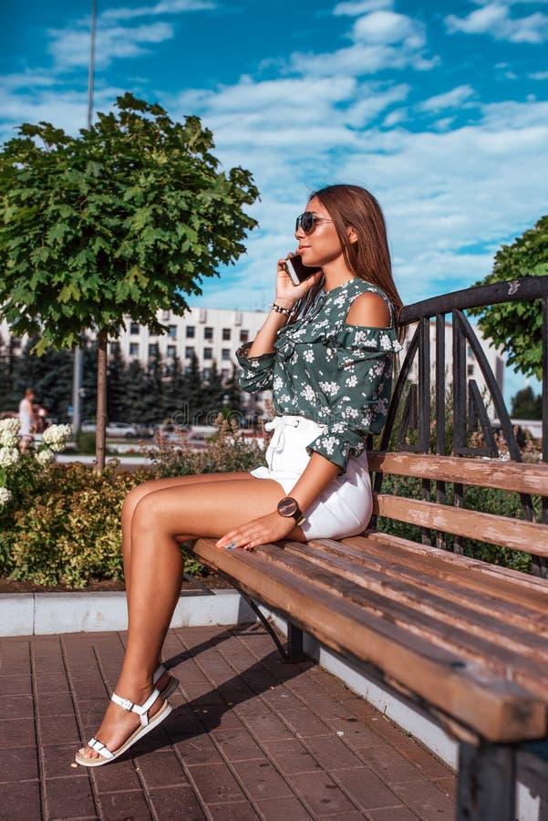 Una ragazza abbronzata sta sedendosi sulla città dell'estate del banco contro un fondo degli alberi, in sua mano è uno smartphone fotografie stock libere da diritti