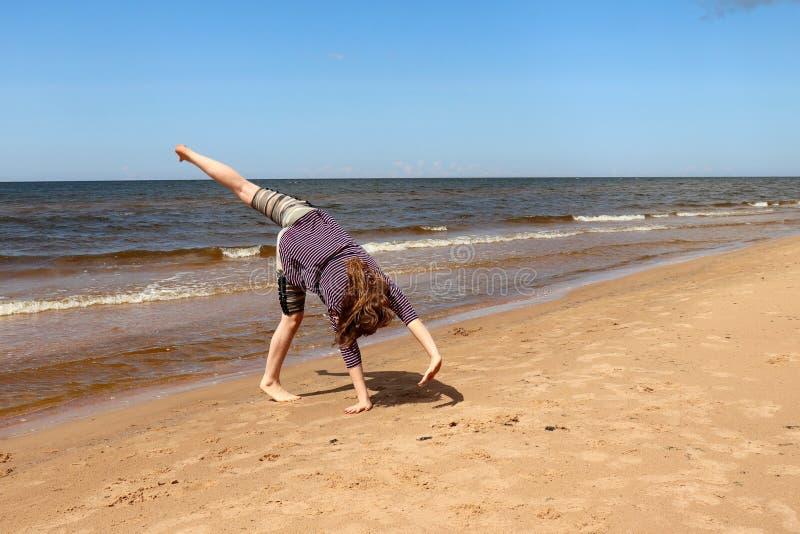 Ragazza Che Fa Cartwheel Sulla Spiaggia Fotografia Stock