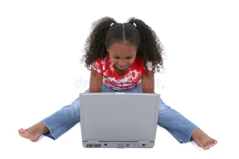Una ragazza adorabile di sei anni che si siede sul pavimento con il computer portatile fotografia stock