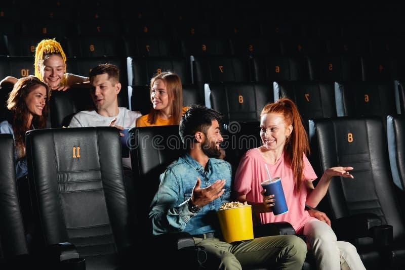 Una ragazza affascinante e un tizio barbuto che parla prima di guardare il film. fotografia stock
