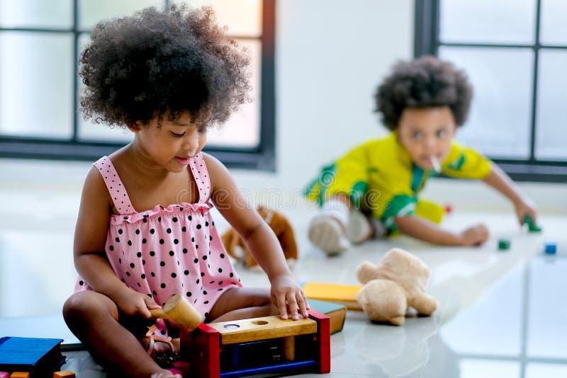 Una ragazza africana della corsa mista sta giocando con i giocattoli davanti all'altro ragazzo e lo sguardo gode di e soddisfatto fotografia stock libera da diritti
