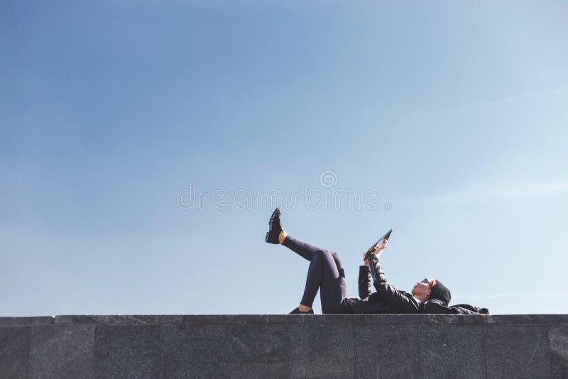 Una ragazza alla moda dei pantaloni a vita bassa si trova su lei indietro con le sue gambe sollevate su un parapetto ed utilizza  immagine stock libera da diritti