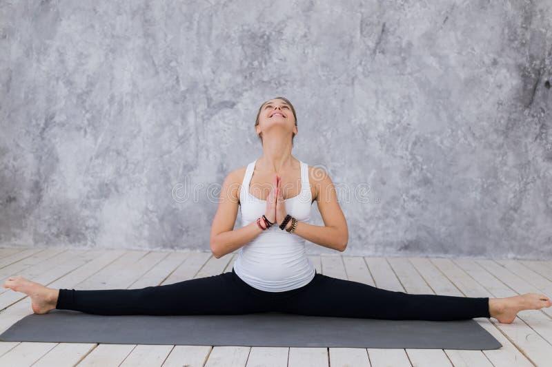 Una ragazza allegra che allunga le gambe, classe di yoga Donna bionda che si siede in cordicella fotografie stock libere da diritti