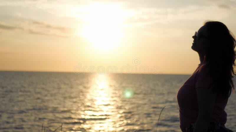 Una ragazza ammira il bello tramonto dal mare, colpi di un vento leggero fotografie stock