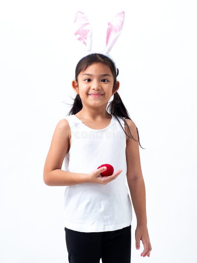 Una ragazza asiatica adorabile che tiene un uovo di Pasqua fotografia stock