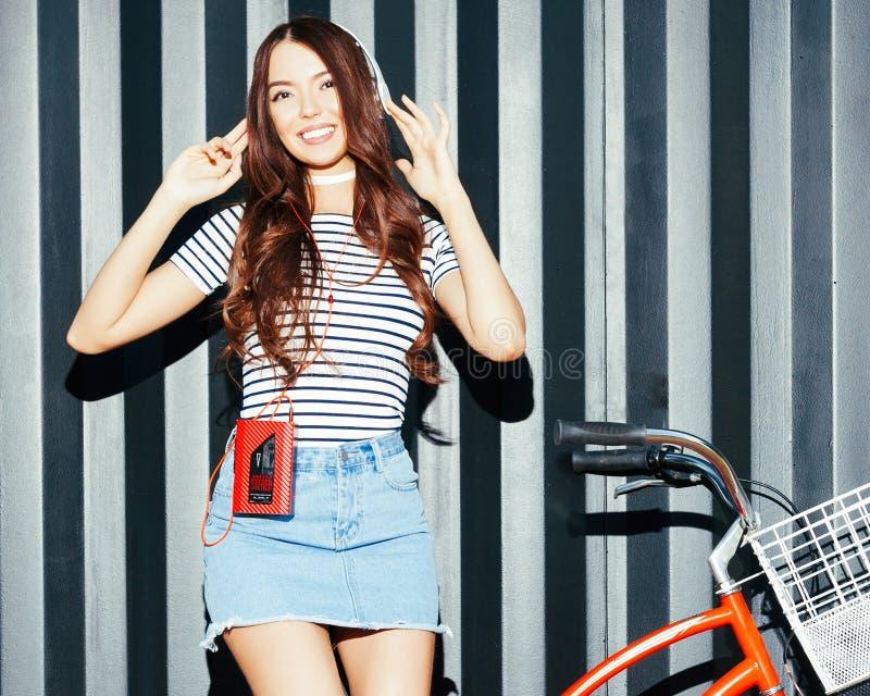 Una ragazza asiatica incredibilmente bella in un'attrezzatura dell'estate gode della musica Cuffie e giranastri d'annata rosso immagine stock