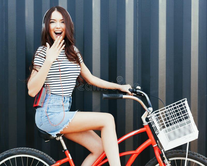 Una ragazza asiatica sbalorditiva in un'attrezzatura dell'estate, in una gonna del denim, con un giranastri e le cuffie si siede  fotografia stock