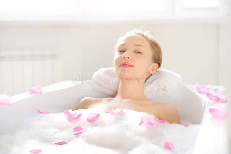 Una ragazza attraente che si rilassa nel bagno fotografia stock libera da diritti