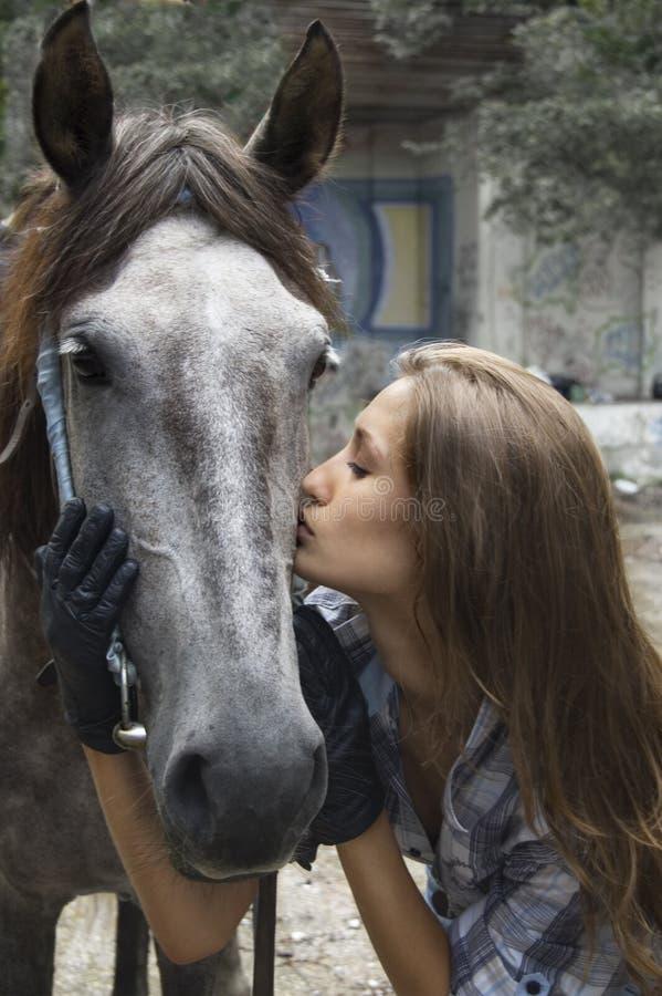 Una ragazza bacia il suo cavallo fotografia stock libera da diritti