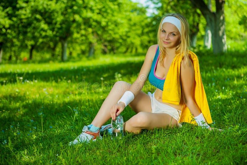 Una ragazza beautyful di sport su erba fotografia stock
