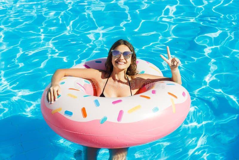 Una ragazza in bikini ed occhiali da sole neri è nella piscina fotografia stock