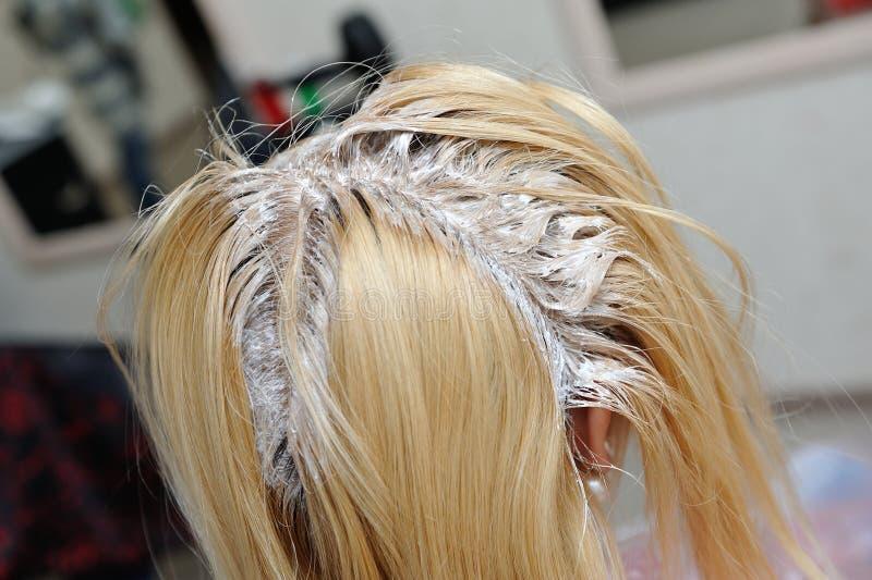 Una ragazza bionda è stata spalmata di pittura sui suoi capelli in un salo di bellezza immagini stock