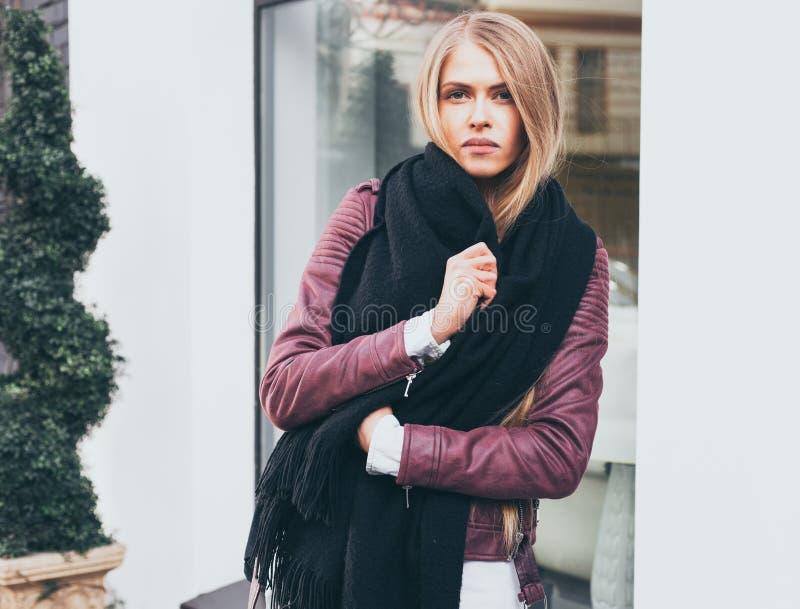 Una ragazza bionda dai capelli lunghi sbalorditiva che posa in vestiti alla moda, un rivestimento, jeans neri all'entrata al rist fotografia stock