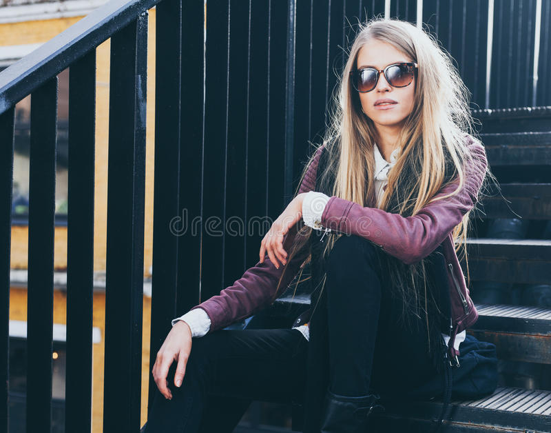Una ragazza bionda dai capelli lunghi sbalorditiva si siede in vestiti ed occhiali da sole d'avanguardia sui punti Goda della vos immagini stock libere da diritti