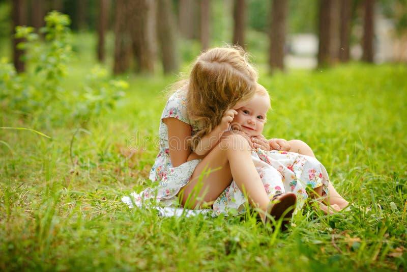 Una ragazza bionda di due sorelle affascinanti che abbraccia e che ride sul gra immagini stock