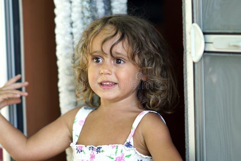 Una ragazza bionda di tre anni guarda avanti immagine stock libera da diritti